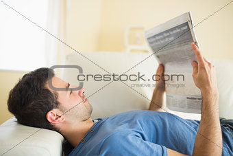 Casual peaceful man lying on couch reading  newspaper