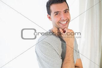 Casual smiling man looking at camera touching chin