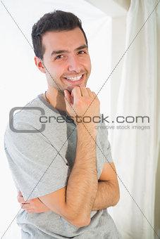 Casual cheerful man looking at camera touching chin