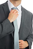 Close up of businessman adjusting blue tie