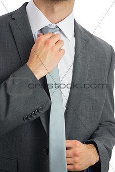 Close up of businessman adjusting blue tie