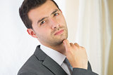 Handsome unsmiling businessman posing at camera