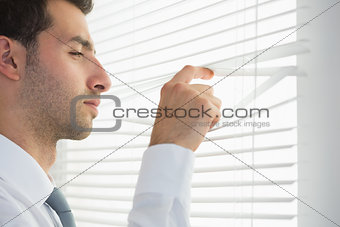 Attractive frowning businessman spying through roller blind