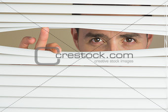 Focused male eyes spying through roller blind