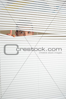 Astonished male eyes spying through roller blind