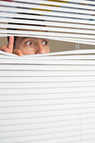 Male eyes spying through roller blind