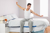 Yawning casual man sitting on bed stretching his arms