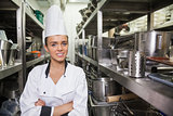 Young cheerful chef standing arms crossed between shelves