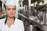 Young unsmiling chef standing arms crossed between shelves