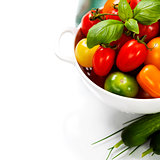 Assorted tomatoes and vegetables in colander