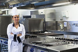 Young happy chef standing next to work surface arms crossed