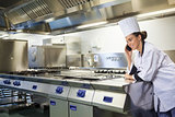 Young happy chef standing next to work surface phoning