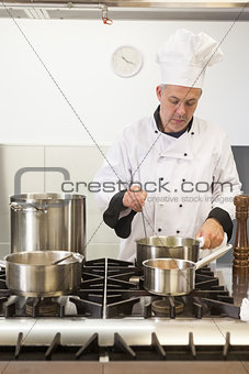 Focused head chef looking into pot