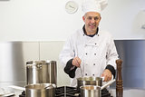 Smiling head chef holding ladle looking at camera