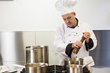 Focused head chef using pepper mill