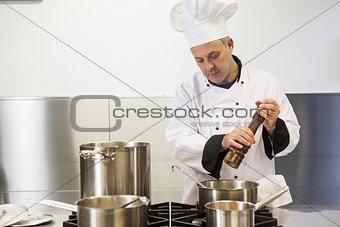 Focused head chef using pepper mill