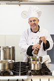 Smiling head chef using pepper mill