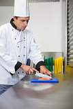 Serious chef cutting raw salmon with knife on blue cutting board