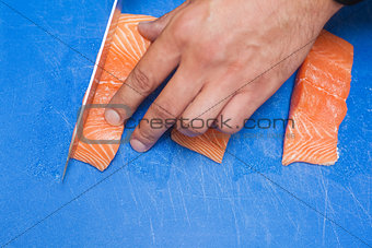 Close up of hand slicing raw salmon with sharp knife