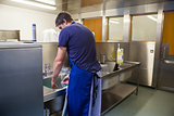 Kitchen porter washing up at sink
