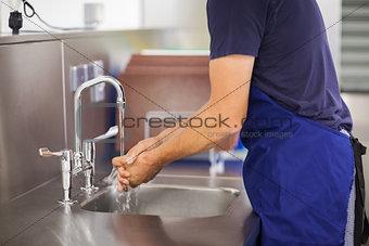 Kitchen porter washing his hands