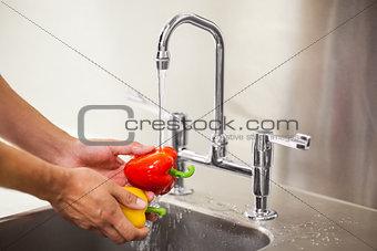 Kitchen porter washing vegetable