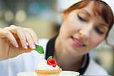 Happy head chef putting mint leaf on little cake