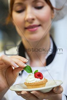Focused head chef putting mint leaf on little cake on plate