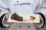 Chef presenting chocolate cake with strawberries