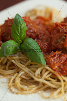 Close up of spaghetti and meatballs with basil leaf