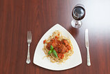 Overhead view of spaghetti and meatballs with basil leaf