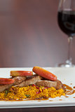 Front view of couscous dish with meat and red wine