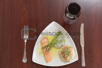 Overhead view of salmon dish with asparagus and red wine