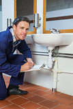 Smiling plumber inspecting sink holding clipboard