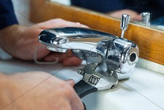 Close up of plumber repairing tap