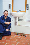 Handsome cheerful plumber sitting next to sink holding wrench