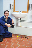 Handsome cheerful plumber sitting next to sink showing thumb up
