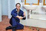 Handsome happy plumber sitting next to sink showing thumb up