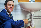Handsome smiling plumber repairing sink
