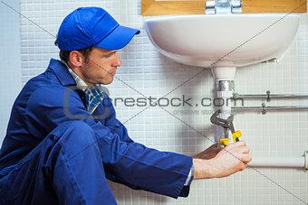 Attractive focused plumber repairing sink