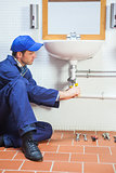 Concentrating plumber repairing sink