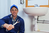 Smiling plumber holding wrench sitting next to sink