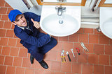 Cheerful plumber repairing sink showing thumb up