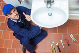 Smiling plumber repairing sink showing thumb up