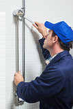 Serious plumber repairing shower head