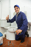 Plumber kneeling next to toilet showing thumb up