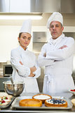 Frowning chef and head chef standing arms crossed