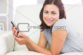 Portrait of young woman lying on her couch in the living room
