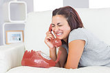 Gorgeous amused woman using a dial phone