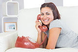 Amused young woman using a red dial phone